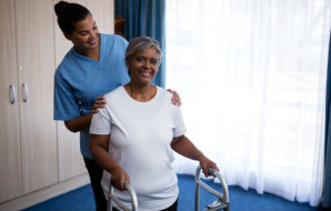 caregiver assisting senior woman while having a physical therapy session